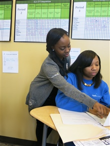 An AmeriCorps member assists a student.